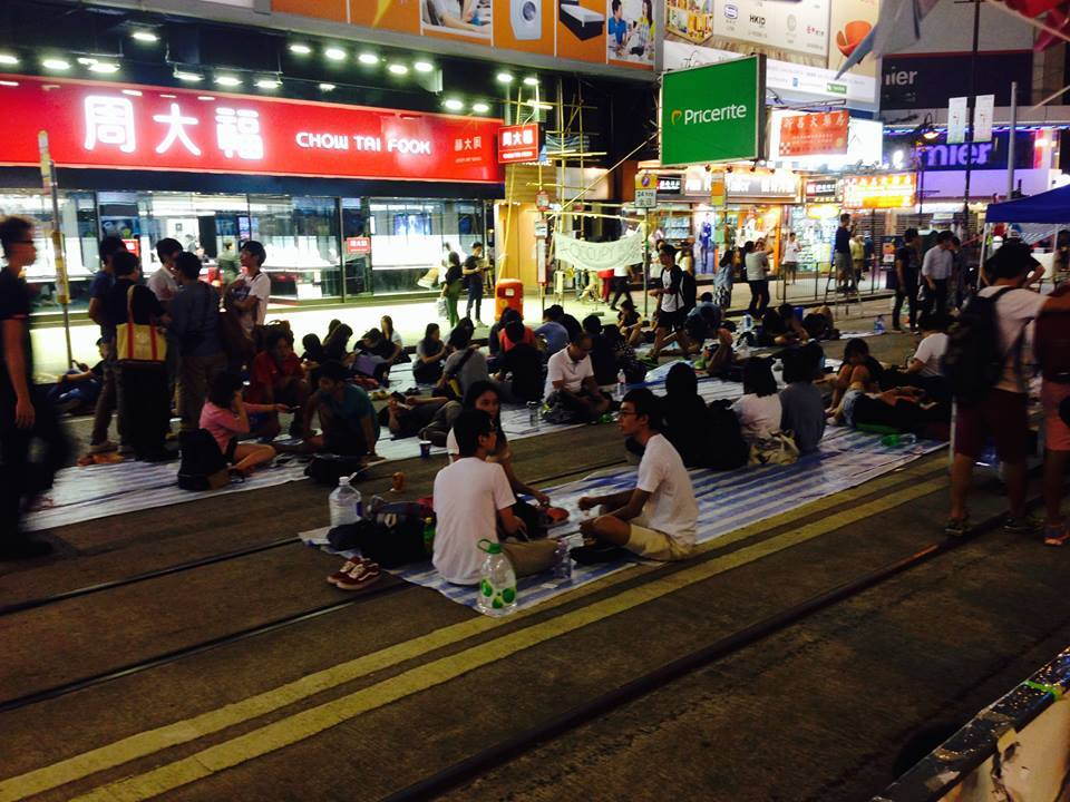 Protesters sitting in the street. Photo Credit: Chin Yi Chow